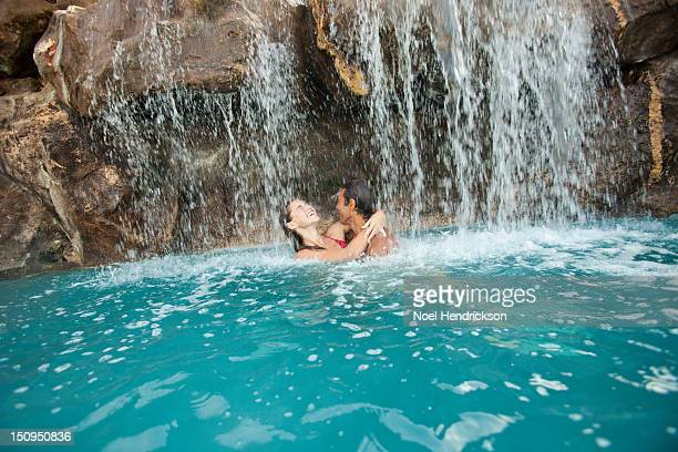 a man and woman embrace in a pool waterfall - water fall hawaii stock pictures, royalty-free photos & images