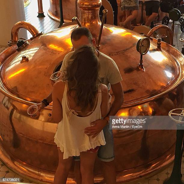 Man And Woman Embracing By Storage Tank In Brewery
