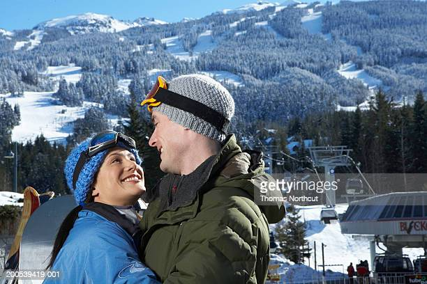 Man and woman embracing on deck overlooking ski lift, side view