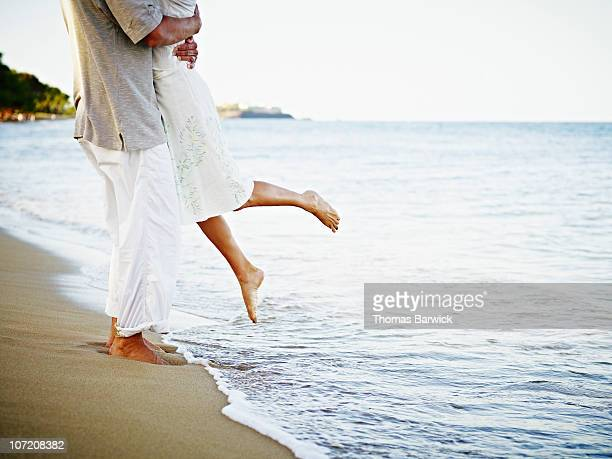 man and woman embracing on tropical beach - human leg stock photos and pictures