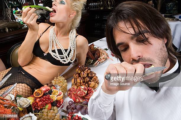 man and woman enjoying a banquet - man eating woman out stock photos and pictures