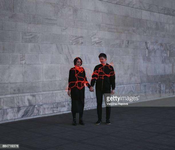 man and woman entangled with neon wires against urban marble background - frau gefesselt stock-fotos und bilder