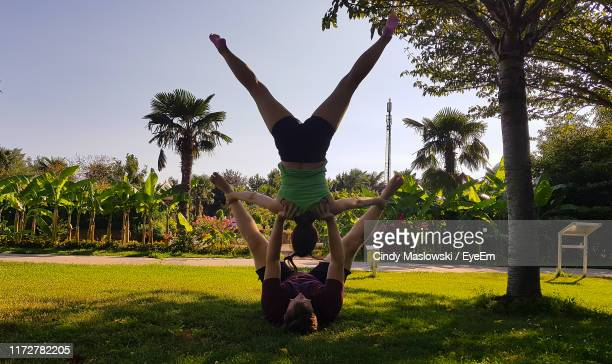 man and woman exercising against trees and sky - maslowski stock-fotos und bilder