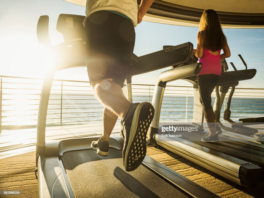 Man and woman exercising on patio over sea : ストックフォト