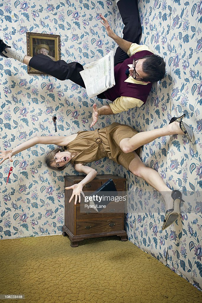 Man and Woman Falling Through The Air in Living Room : Stock Photo