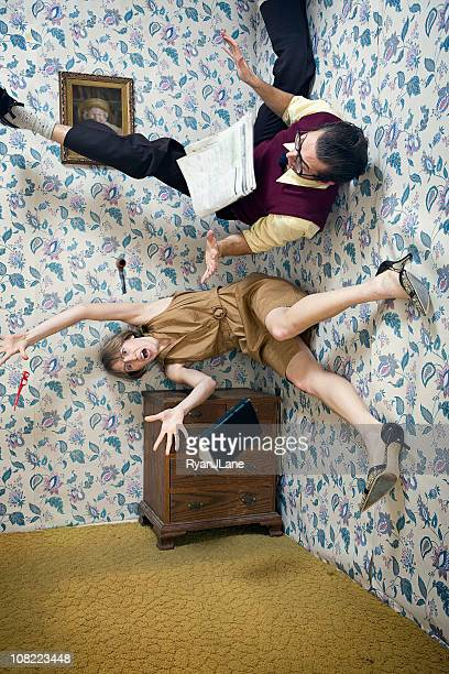 man and woman falling through the air in living room - freaky couples stock photos and pictures
