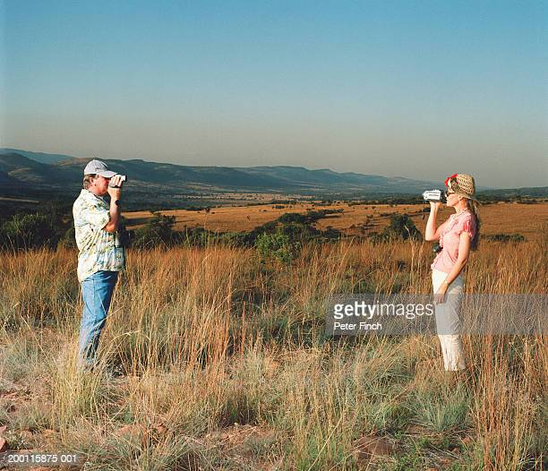 Man and woman filming each other in savannah landscape