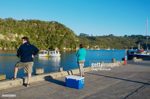 Man and woman fishing as a ferry crosses Whitianga Harbour.