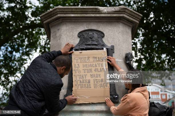 A man and woman fix a cardboard sign saying this plaque is dedicated to the slaves that were taken from their homes to the Edward Colston statue...