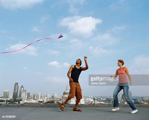 man and woman flying a kite on a roof against a skyline of london - nur erwachsene stock-fotos und bilder