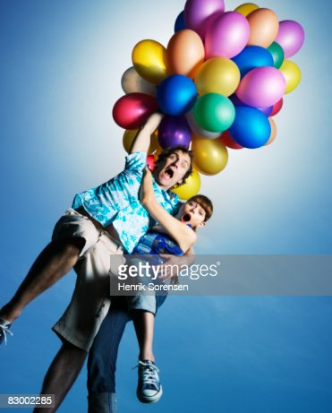 Man And Woman Flying Away Holding A Lot Of Balloon Stock ...
