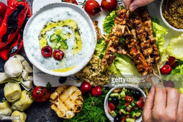 Man and woman getting chicken skewers from a board with lots of snacks and a bowl of yogurt and cucumber dip.