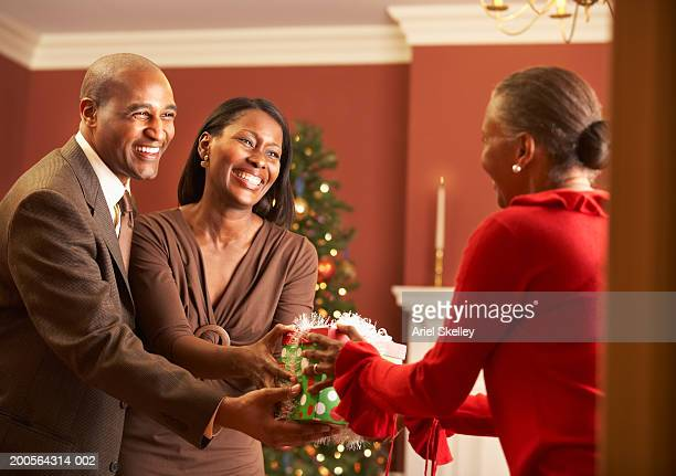 man and woman giving christmas gifts to mother, smiling - african american christmas images stock pictures, royalty-free photos & images