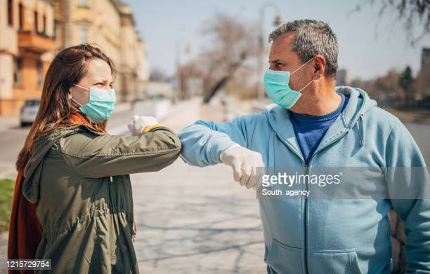 man and woman greeting each other with elbows instead of handshake - elbow bump stock pictures, royalty-free photos & images