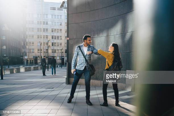 man and woman greeting with elbows - social distancing stock pictures, royalty-free photos & images