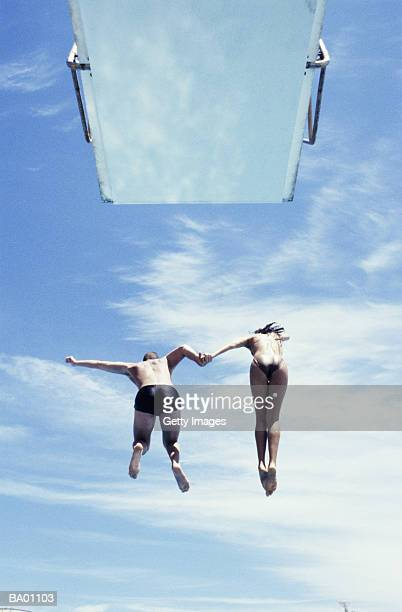 Man and woman hand in hand jumping off diving platform