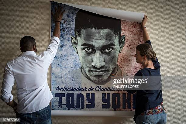 A man and woman hang a poster of France's gold medalist in boxing at the 2016 Rio Olympics Tony Yoka on August 29 2016 in ChantelouplesVignes / AFP /...
