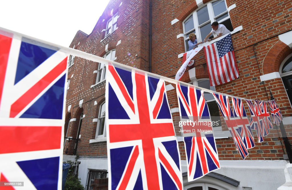 A man and woman hang a United States flag and a Californian state flag outside their house on the Royal procession route on May 18, 2018 in Windsor, England. The Berkshire town, west of London will host the wedding of Prince Harry to Ms. Meghan Markle in front of tens of thousands of royal fans on May 19, 2018 where HRH Prince Charles, father to Harry will accompany Ms. Markle down the aisle of the Quire of St. George's chapel on her Wedding Day.