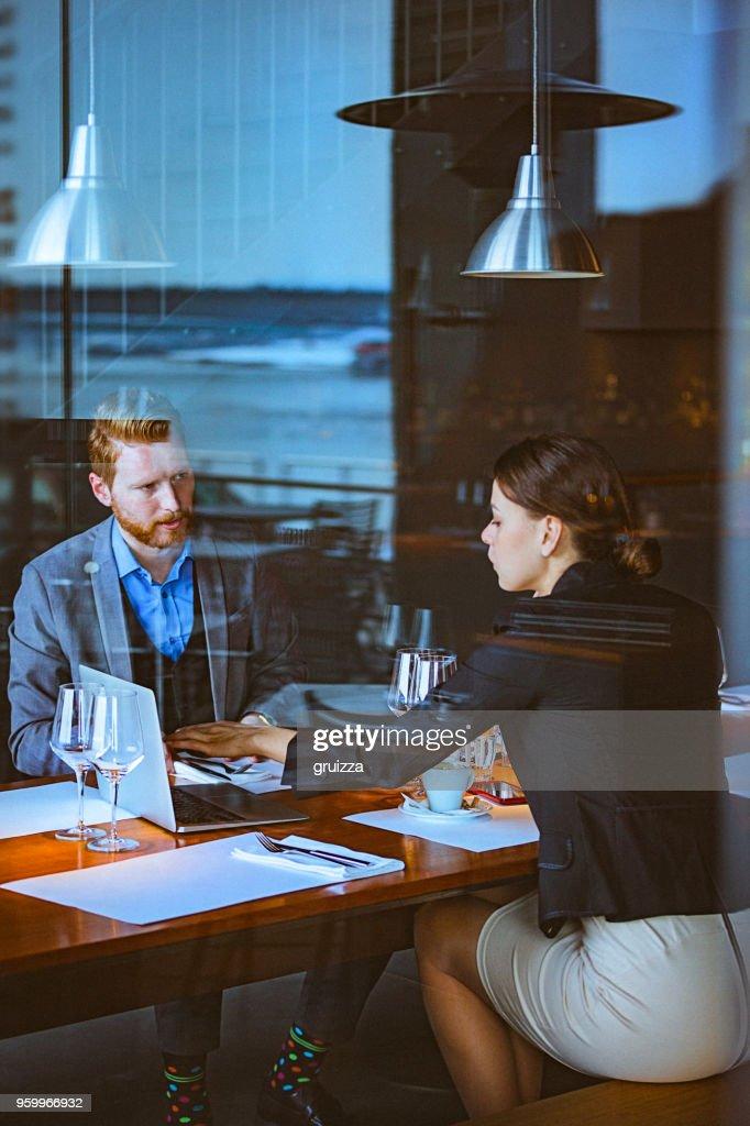 Mann und Frau, die ein Geschäftstreffen in der Mittagszeit in ein Cafe / Restaurant : Stock-Foto