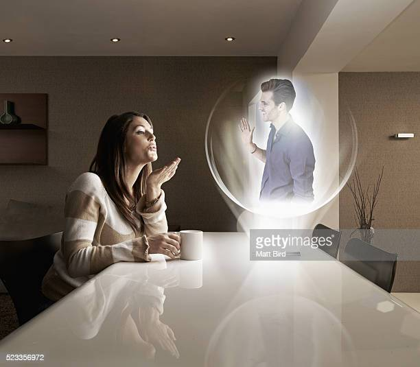 man and woman having a video call using futuristic 3d device - hologram stock pictures, royalty-free photos & images