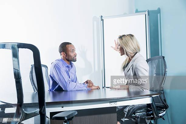 Man and woman having business meeting in boardroom