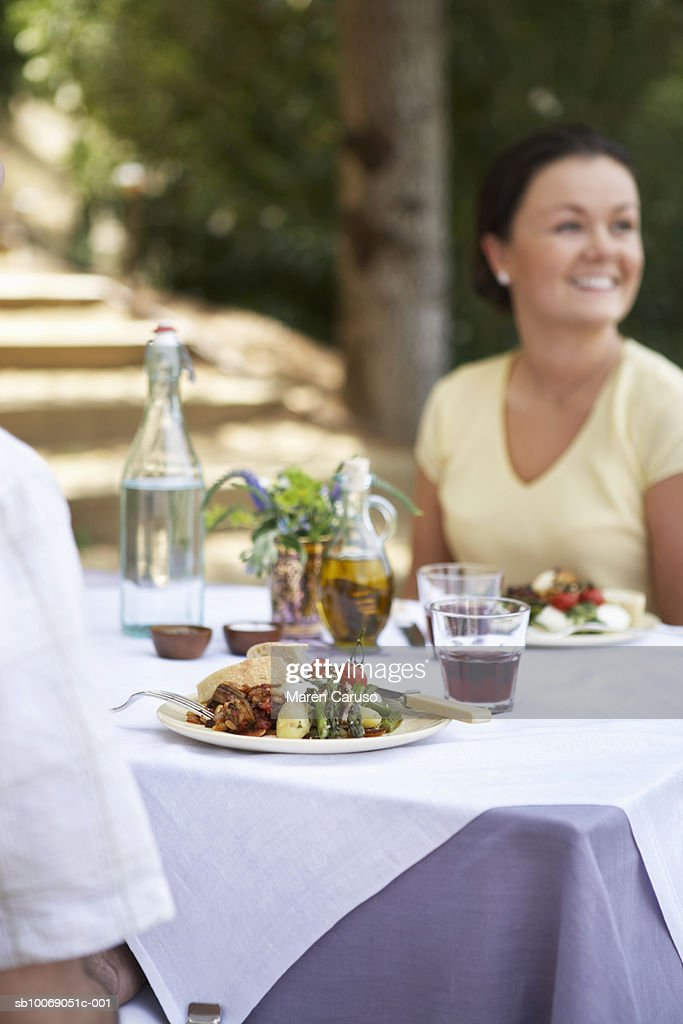 Man and woman having dinner outdoor party, focus on food on table : Stockfoto