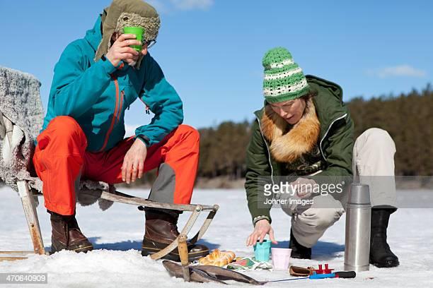 Man and woman having food while fishing