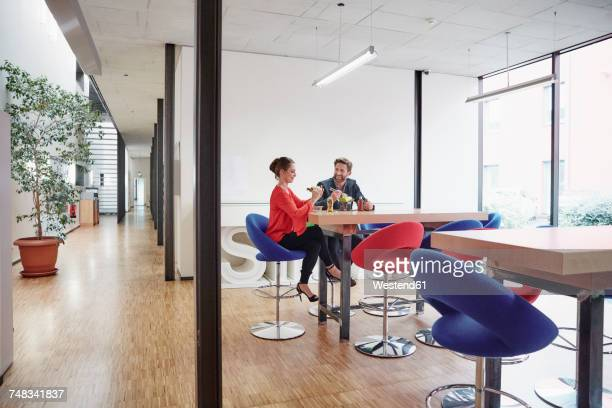 Man and woman having lunch break in office