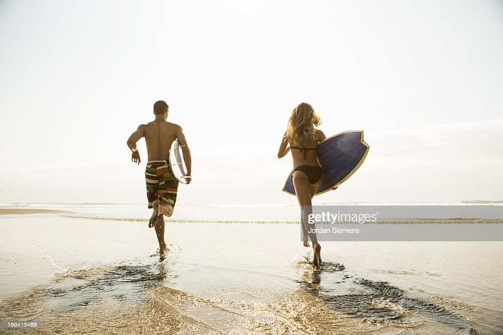 A man and woman heading out surfing. : Stock Photo