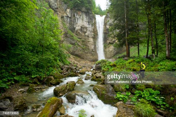 Man and woman hiking in next to scenic waterfall