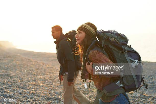 Man and woman hiking on beach with rucksacks.