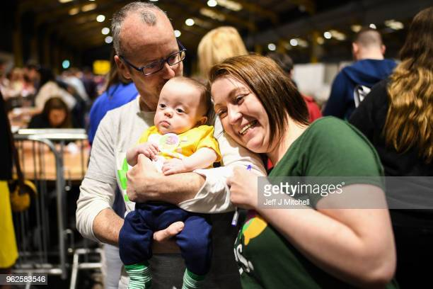 A man and woman hold a young child as the count in the Irish referendum on the 8th amendment concerning the country's abortion laws takes place at...
