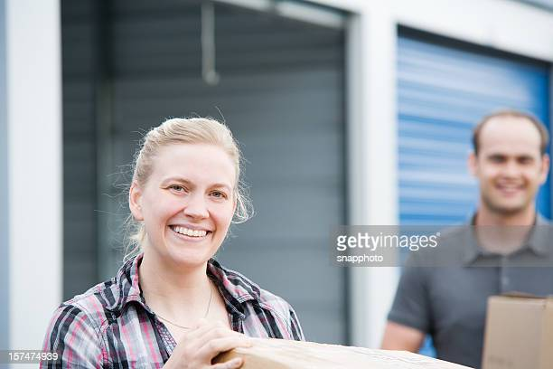man and woman holding boxes at self storage unit - self storage stock pictures, royalty-free photos & images