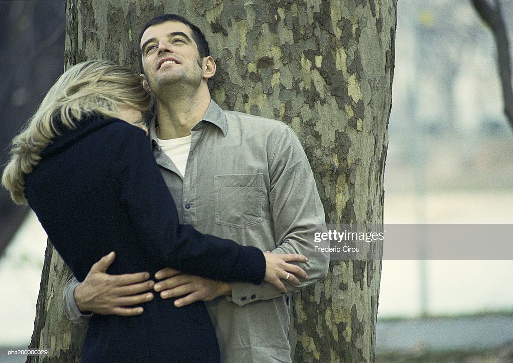 Man and woman holding each other, leaning against tree. : Stockfoto