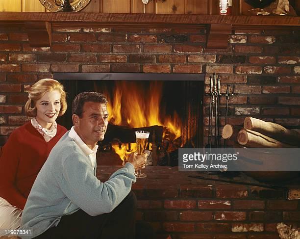 の男性と女性の近くに暖炉を持つガラスて先