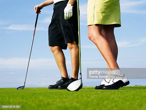 Man and woman holding golf clubs on golf course, low section