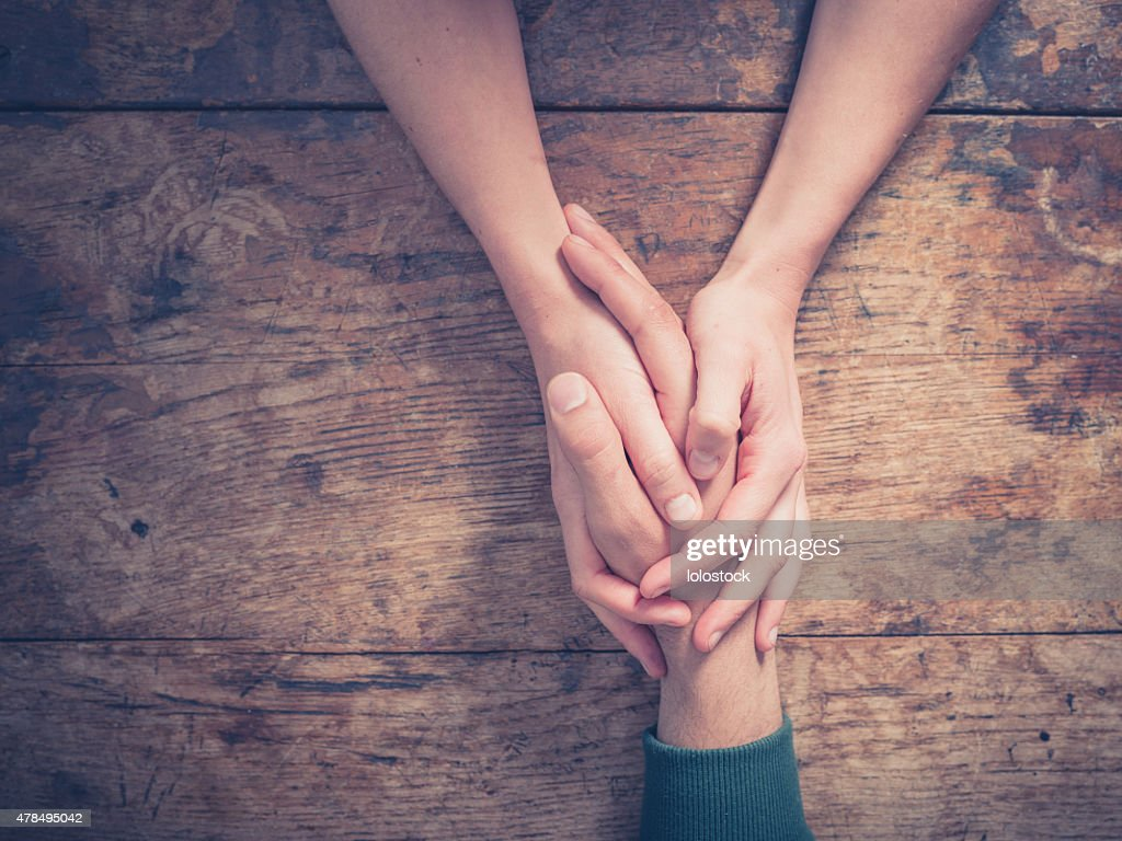 Man and woman holding hands at a table : Stock Photo