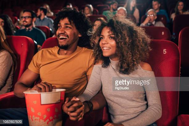 man and woman holding hands at cinema - girlfriends films stock pictures, royalty-free photos & images