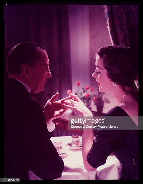 Man and woman holding hands at the dinner table c 1950 Photographic Advertising Limited founded in 1926 created multipurpose stock images with the...