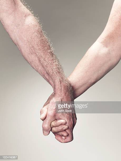 Man and woman holding hands, close-up of hands