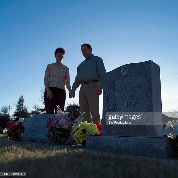 Man and woman holding hands in cemetery (focus on tombstone)