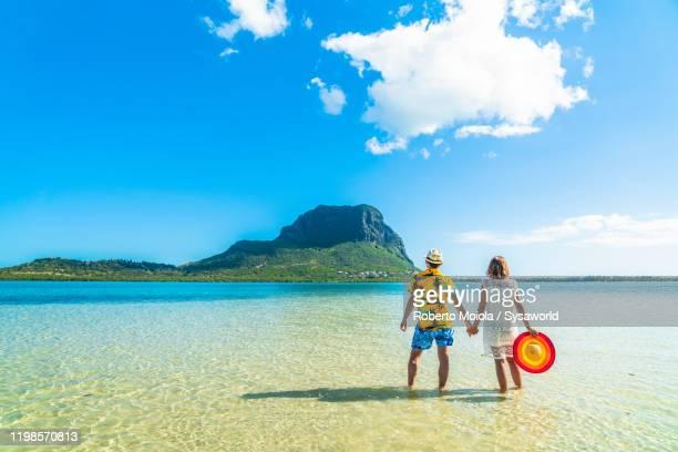 man and woman holding hands in the tropical lagoon, indian ocean, mauritius - islas mauricio fotografías e imágenes de stock
