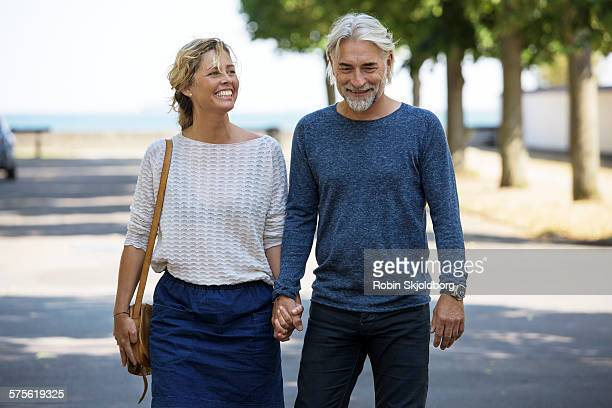 Man and woman holding hands laughing