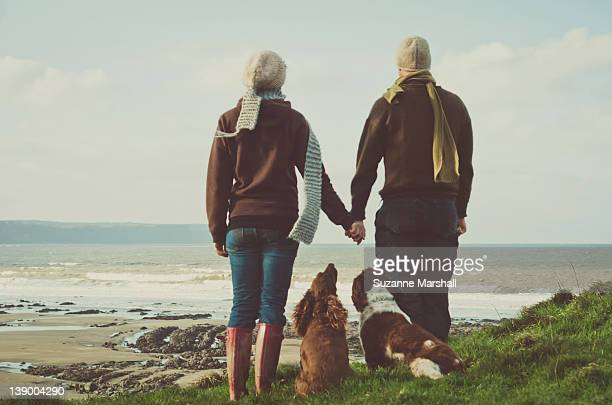 Man and woman holding hands looking out to sea
