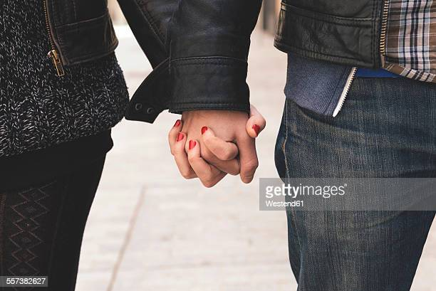 Man and woman holding hands on the street