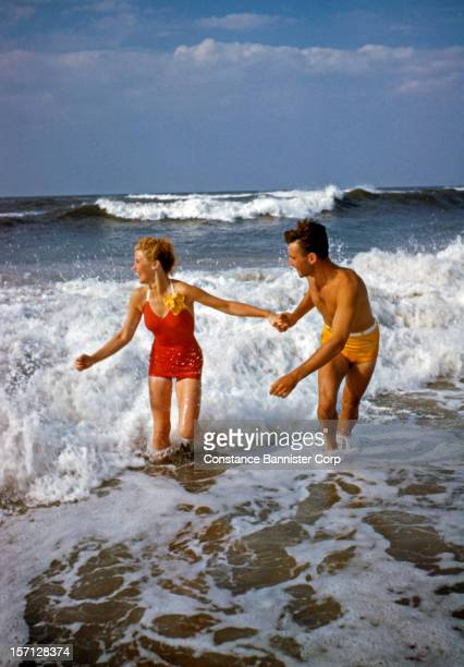 A man and woman holding hands playing in the ocean surf New York State 1947