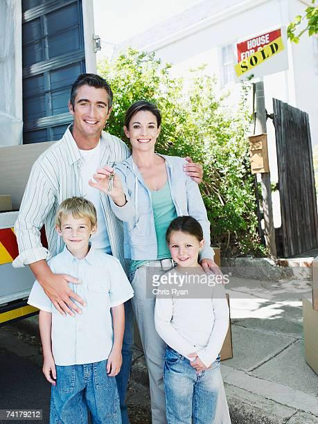 Homem e mulher segurando as chaves na frente de casa com
