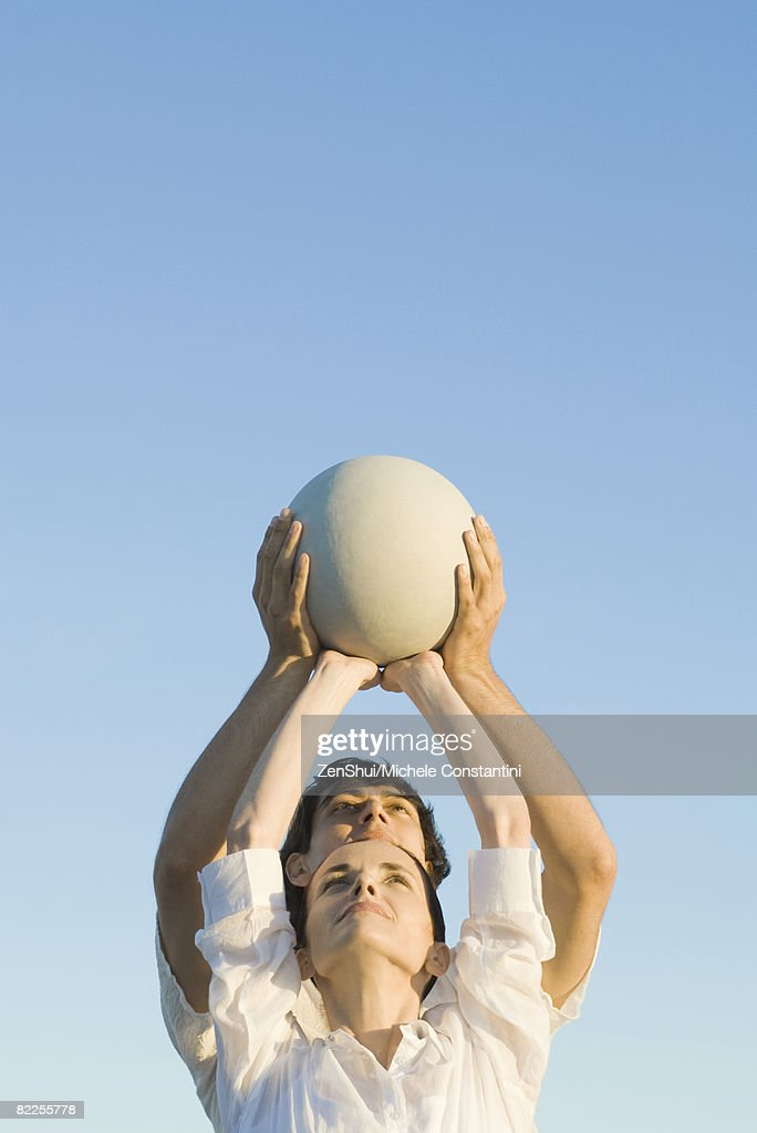 Man and woman holding up fitness ball together : Stock Photo