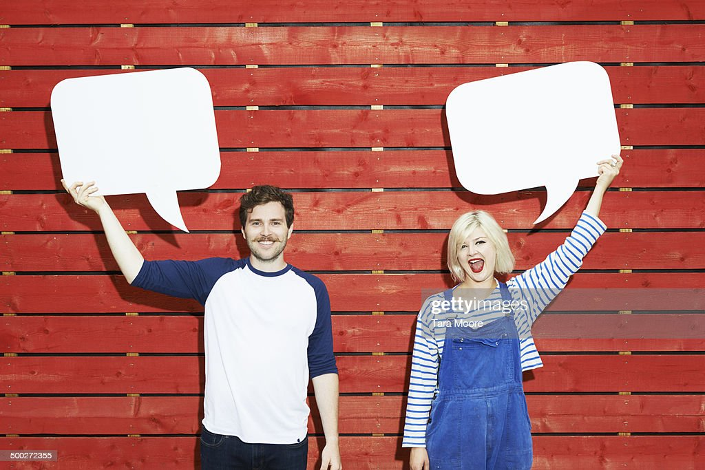 man and woman holding up speech bubbles : Stock Photo