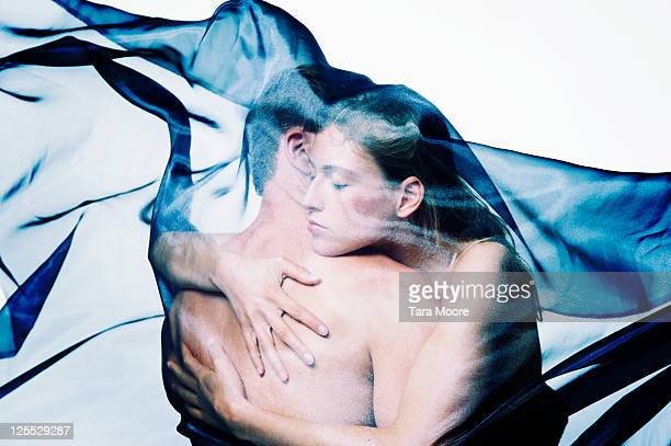 man and woman hugging covered by material